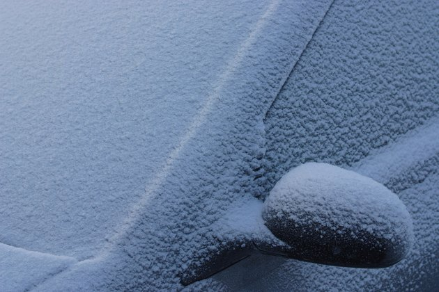Frozen car covered in snow