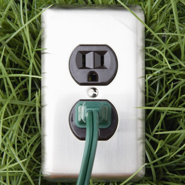 Electrical outlet in grass with power cord