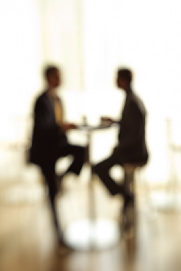 Blurred silhouette of businessmen at table