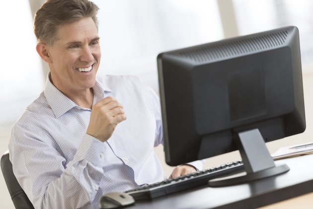Happy Businessman Looking At Computer Monitor