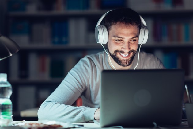 Smiling man networking late at night