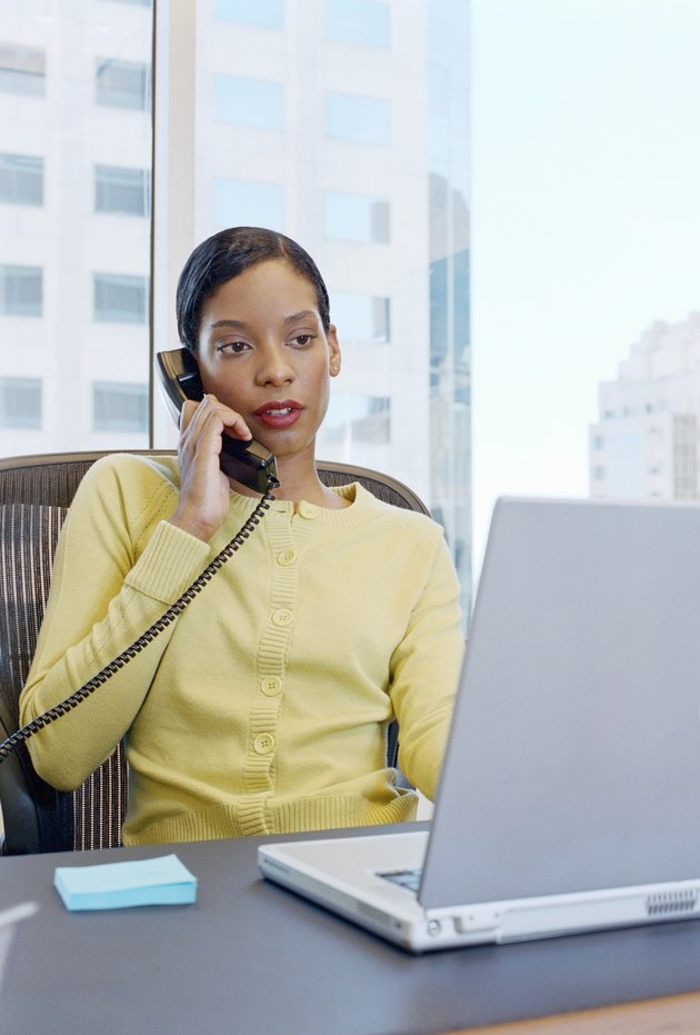 Young female office worker using telephone and laptop computer