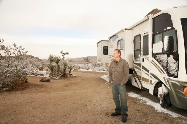 Man standing by motor home in desert with melting snow