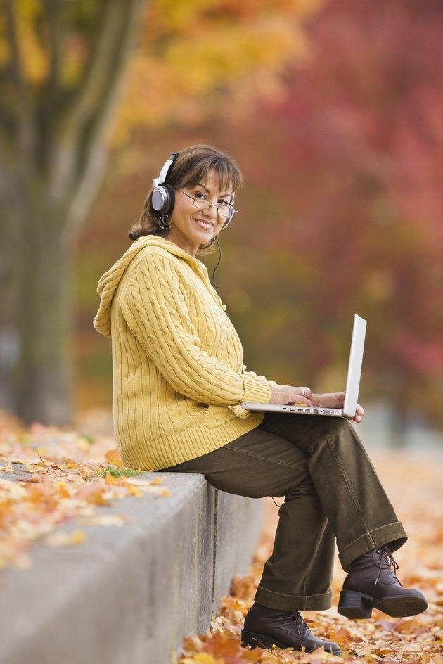 Hispanic woman using laptop outdoors with headphones