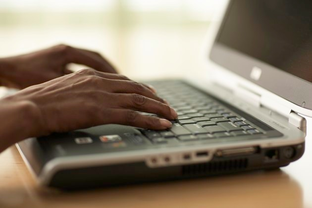Senior woman using laptop, close-up of hands
