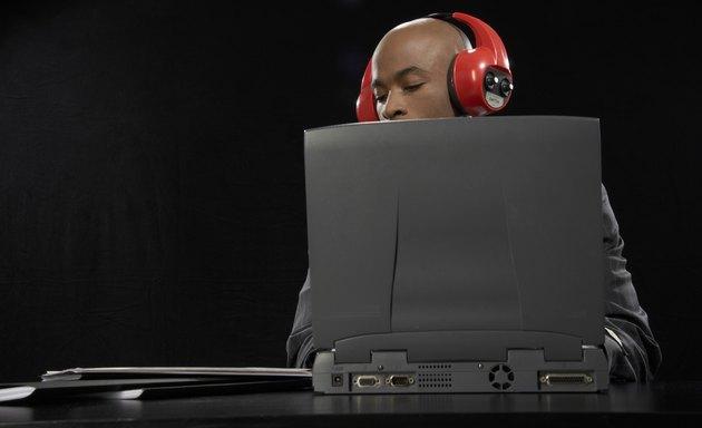 Businessman wearing headphones using laptop at desk