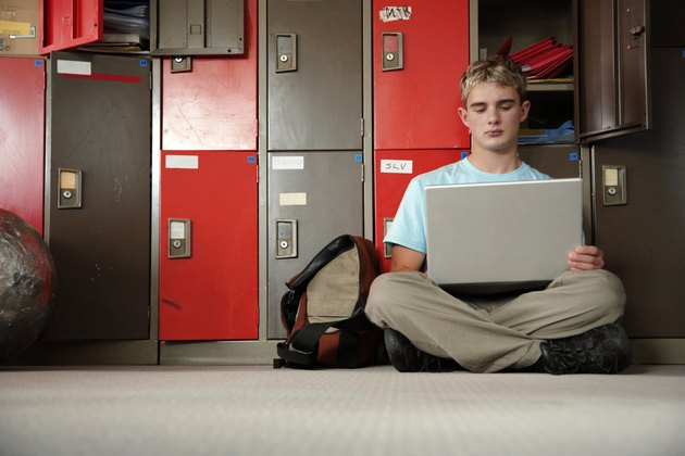 Young man using laptop sitting cross-legged on floor by lockers