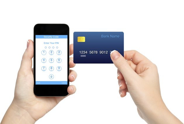 female hands holding phone and credit card