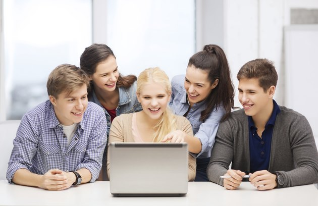 smiling students looking to laptop at school