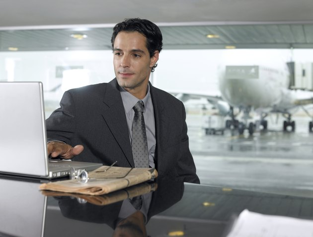 Businessman using laptop computer in airport, close-up