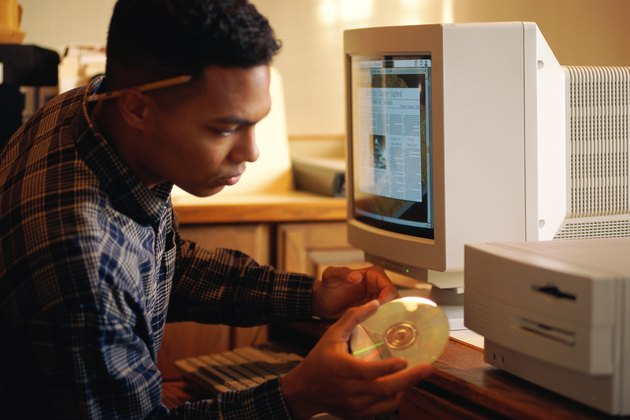 Man putting compact disc into computer