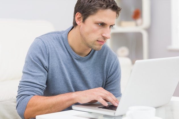 Serious young man using laptop in living room