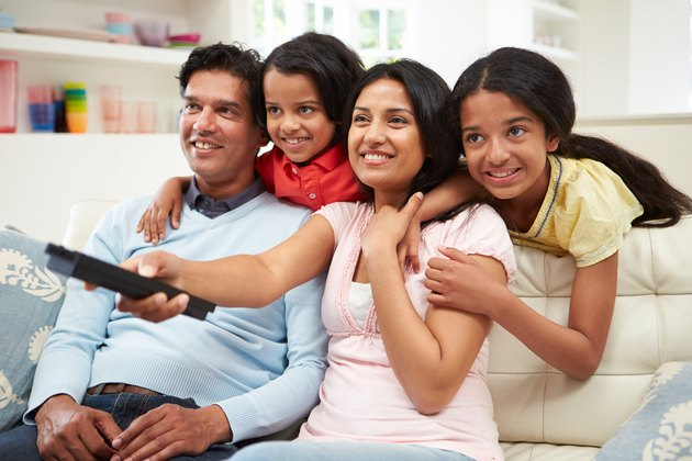 An Indian family sitting on the sofa watching television