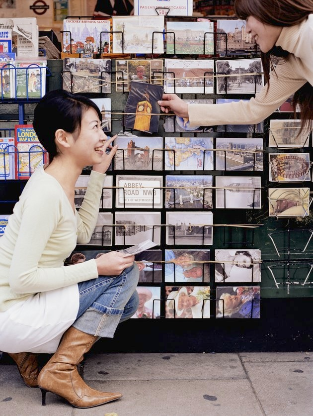 Two young women by souvenir stall, choosing postcards