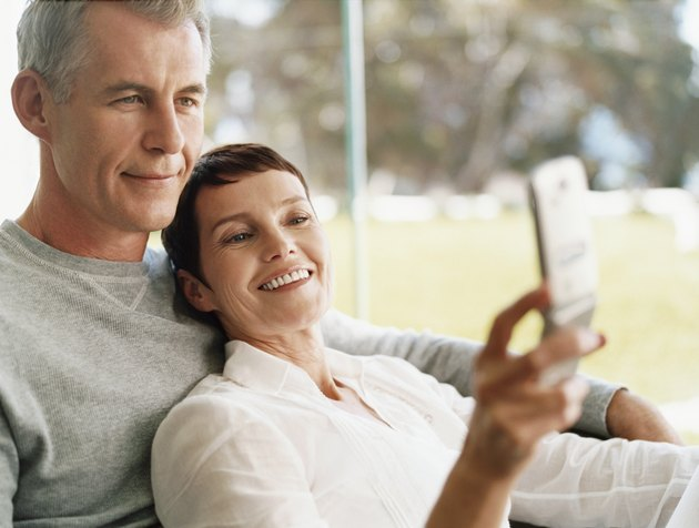 Mature Couple Sit Together Looking at a Mobile Phone