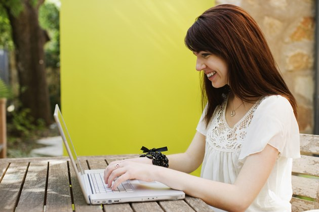 Woman working on a laptop and smiling