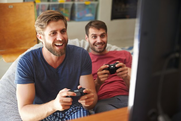 Two Male Friends In Pajamas Playing Video Game Together