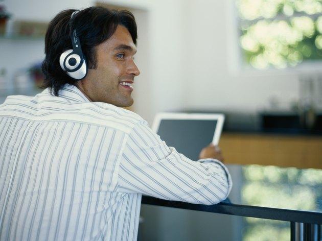 Young man wearing headphones using laptop, looking away, rear view