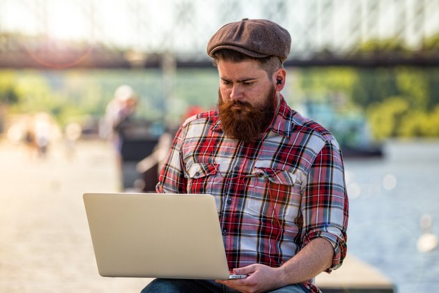 Trendy hipster young man with laptop