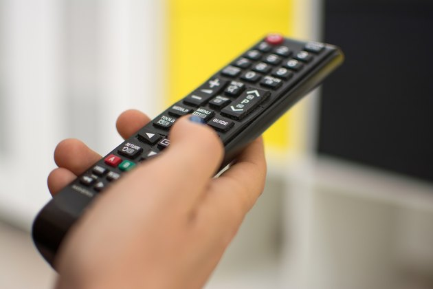 Close up of a hand holding a television remote control.