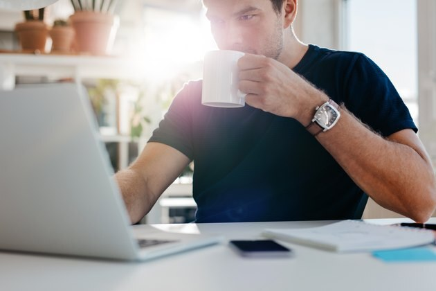 Young businessman with cup of coffee at work