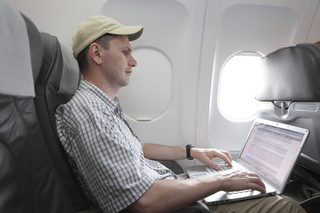 Passenger with laptop in airplane