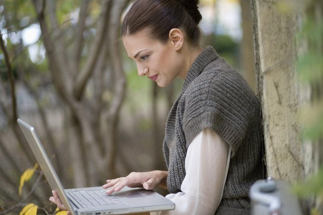 Side view of young businesswoman using laptop in yard
