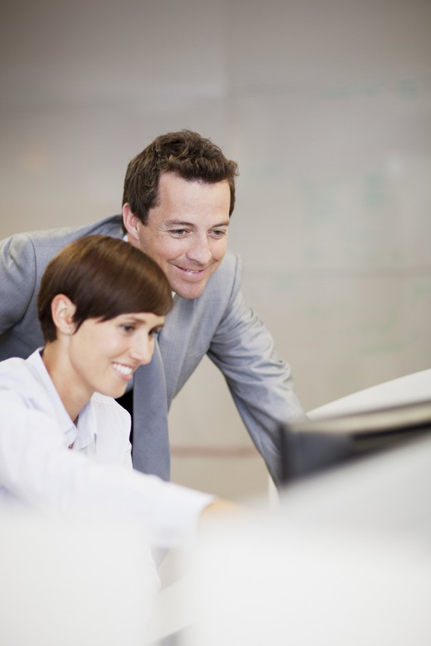 Smiling businessman and businesswoman using computer