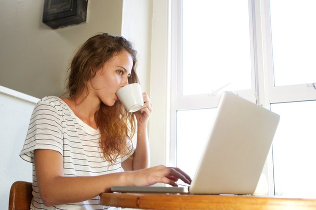 Young woman working on laptop and drinking coffee