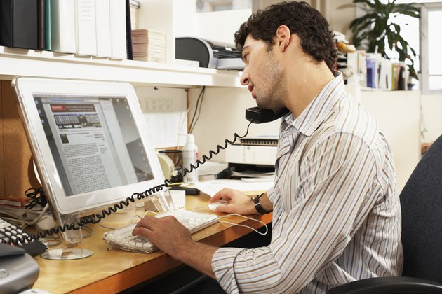 Male office worker balancing phone on shoulder, looking at computer