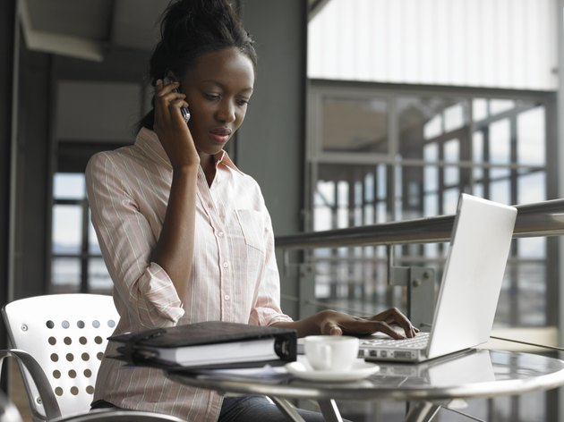 Young businesswoman sitting using laptop and mobile phone