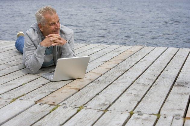 Senior man lying on pier in front of laptop, smiling