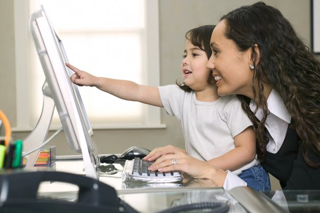 lifestyle shot of a young adult mother as she and her daughter use her computer