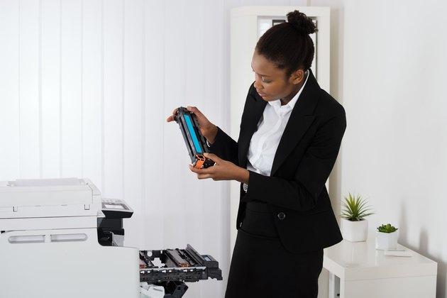 Businesswoman Fixing Cartridge In Office