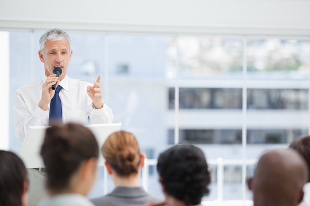 Mature businessman using a microphone to talk to his colleagues