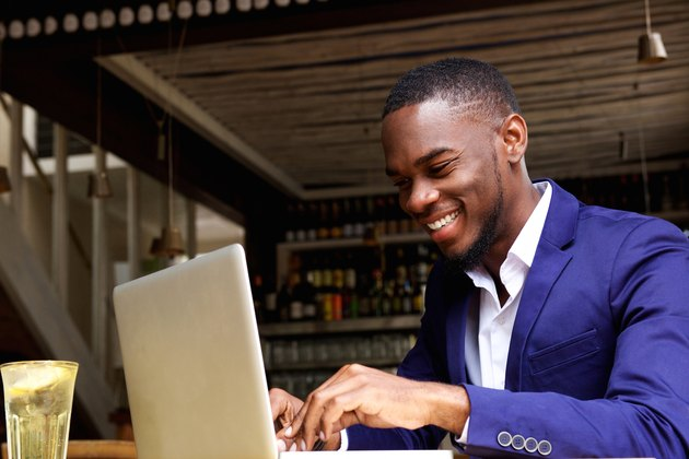 Smiling african businessman working on laptop at cafe