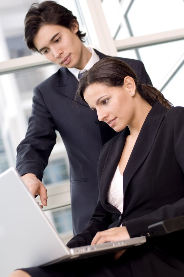 Side profile of a businesswoman and a businessman looking at a laptop