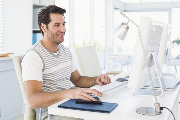 Smiling casual young man using computer