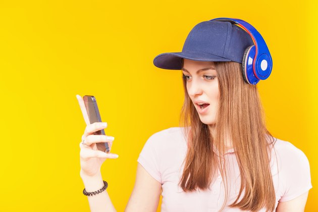Surprised teenage girl uses a headphones and mobile phone