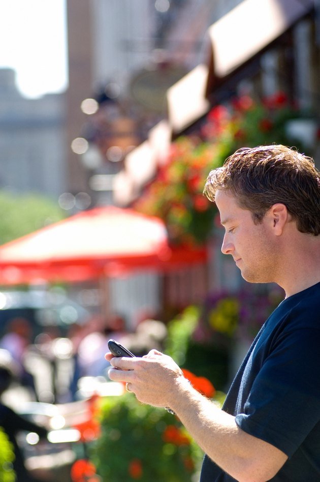 Man using cellular PDA in front of summer street cafe.