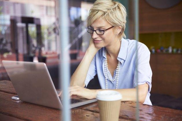 Businesswoman Working On Laptop In Coffee Shop
