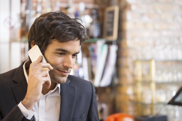 Handsome man calling with a cell phone in coffee bar