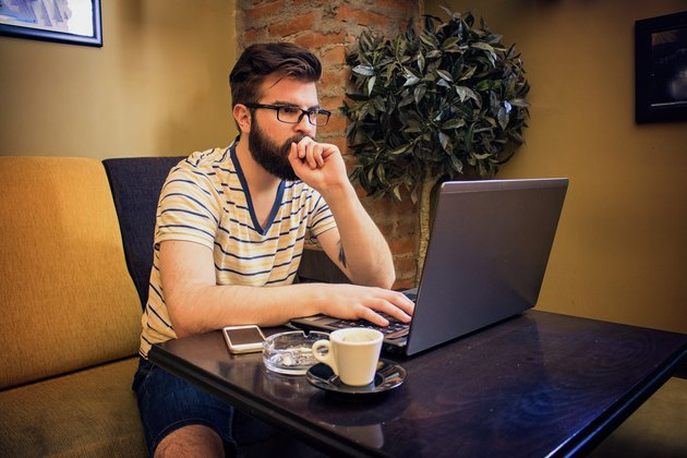 Cheerful Young Man Using Laptop In Coffee Shop