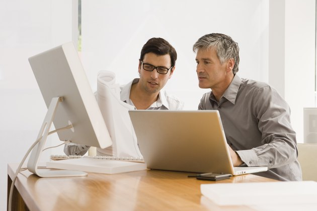 Two businessmen discussing a blueprint in an office