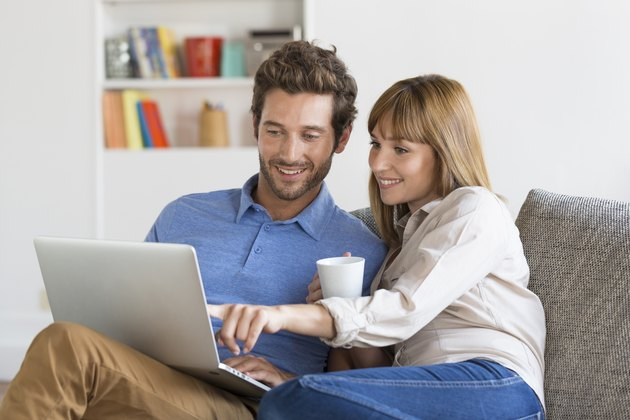 Young couple surfing on internet with laptop.