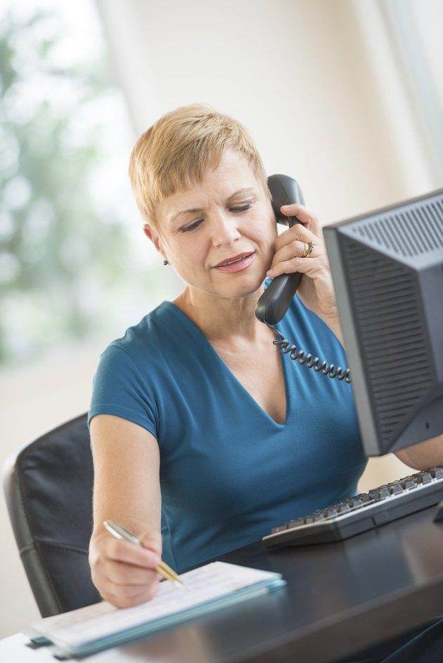 Businesswoman Using Landline Phone While Working At Desk