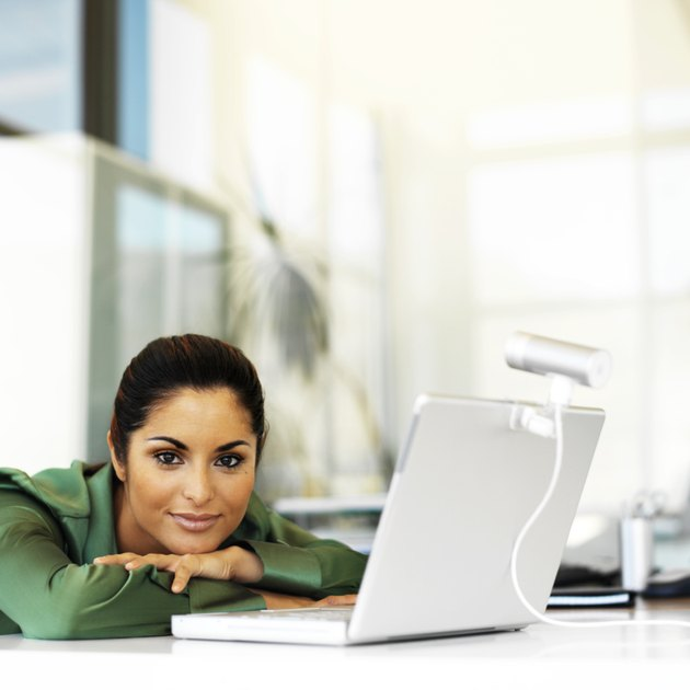 portrait of a young woman leaning forward on the table with a laptop in front of her