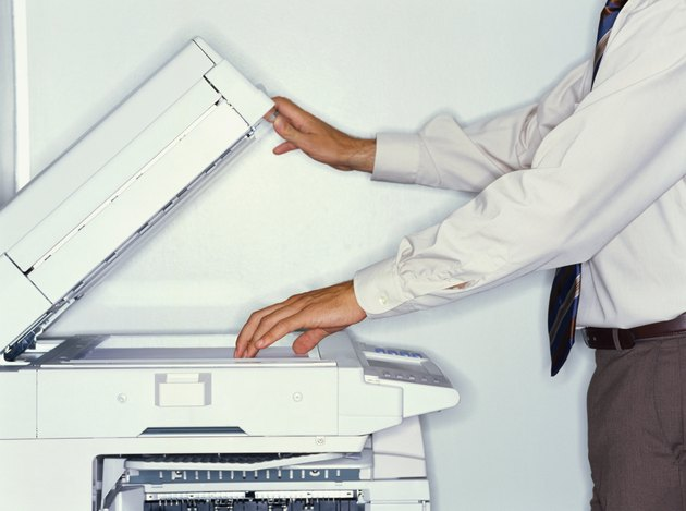 midsection view of a businessman operating a photocopier in an office