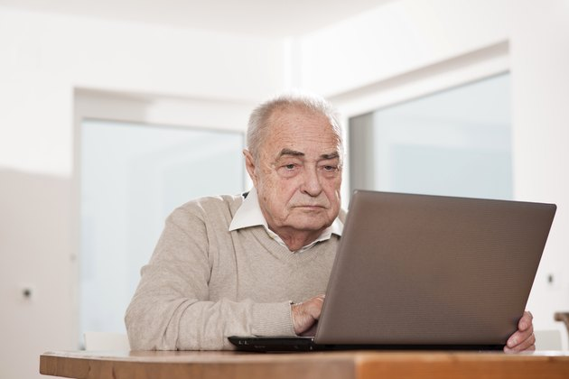 Senior man using laptop at table