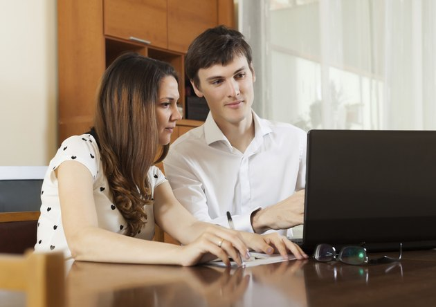 Young couple looking financial documents in laptop